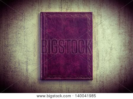 purple book on a grey grunge background top view. tinted photo with vignetting retro toned image