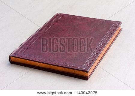 purple book with gold pages on the gray background close-up