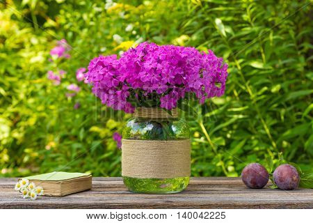 bouquet of phlox flowers in a glass vase ripe plums and old book with daisies on the table on nature background selective focus