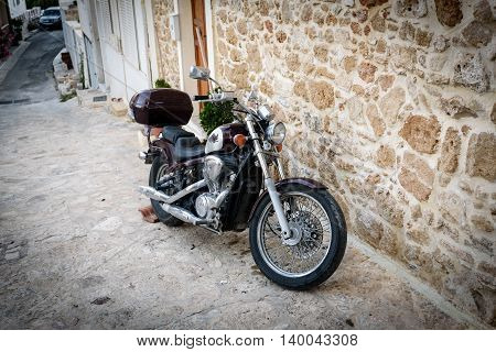 CHANIA, CRETE, GREECE - JULY 2016: Vintage chopper bike stays parked near brick wall in Chania town on Crete island