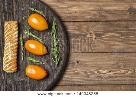Yellow tomato with pie on a wooden Board, place for text