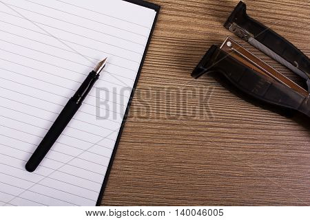 Lay Flat Image Of A Notebook And Stapler On A Wooden Surface