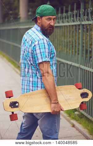 Bearded hipster man posing with longboard and on fashionable green cap