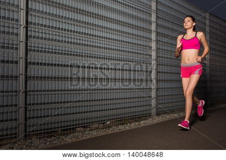 Running woman. Runner jogging against the background of a gray wall. Female fitness model training outside