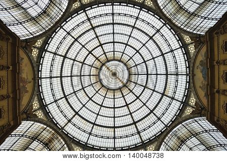 MILAN, ITALY - APRIL 30: Glass roof of Vittorio Emmanuele II shopping gallery on April 30, 2013 in Milan, Italy. Built in 1875 this gallery is one of the most popular shopping areas in Milan.