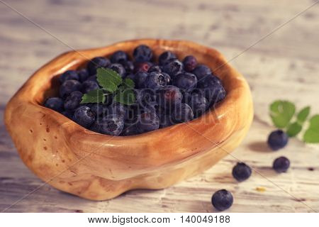 Close up of a wooden bowl full with blueberry toned with blue filter
