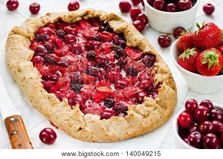 Rye dough galeta pie with fresh strawberry cherry and blackberry selective focus