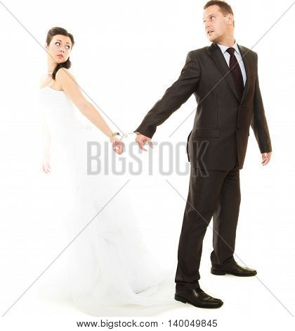 Relationship in married couple. Bride and groom with handcuffs on their hands isolated on white.