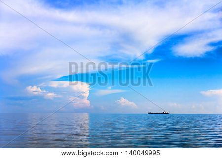 Sea and cloudy sky landscape with alone cargo ship on horizon distance.