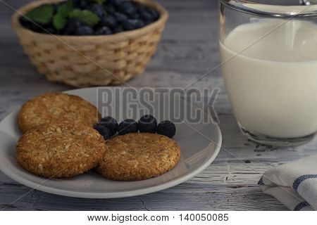Close up of oatmeal cookies with a cup of milk and blueberry on wooden table.