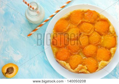 Tarte tatin with apricots on blue background top view