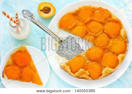 Apricot tarte tatin on blue background top view