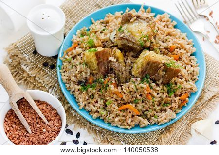 Pilaf from rice devzira with lamb spices and vegetables. Traditional pilaf on the table with ingredients selective focus
