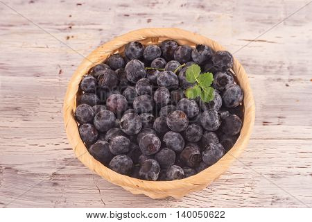 Close up of a small wicker basket full with blueberry