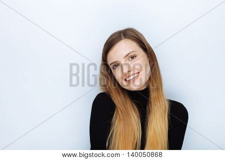 Portrait Of Happy Smiling Young Beautiful Woman In Black Sweater Posing Against White Studio Backgro