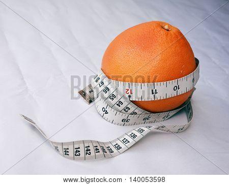 Centimeter wrapped around orange on a white background