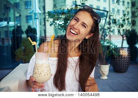 Cheerful young lady is having a good time in cafe in downtown drinking cocktail on open terrace