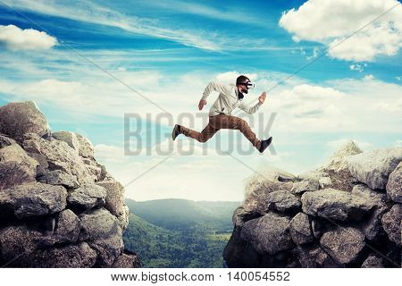Young man in casual clothes and virtual reality headset is jumping between two high rocks on the background of blue sky and green valley