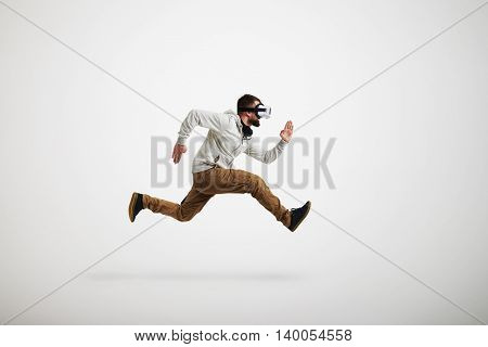 Young bearded man in virtual reality headset is photographed in mid-air jump isolated on white background