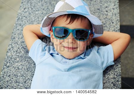 Close-up of small boy in sunglasses and hat who is lying with hands under his head on street stairs parapet and smiling