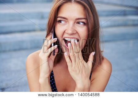 Beautiful girl is speaking on the mobile phone with a broad smile playfully covering her mouth with hand