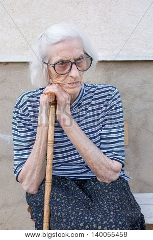 Senior Women Supporting On A Walking Cane