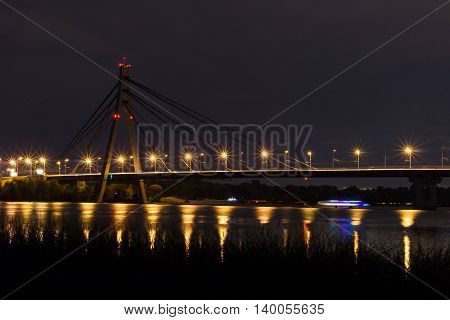 Night bridge above river with reflecting lights