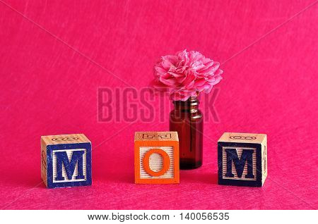 The word mom spelled with alphabet blocks against a pink background with a pink flower