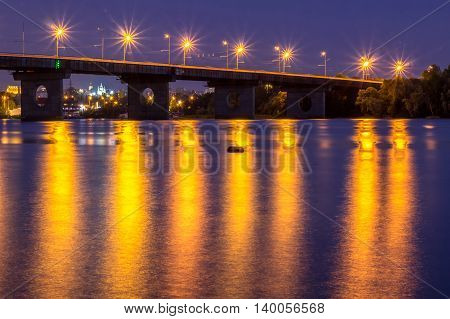 Night bridge lights reflected in river water. HDR
