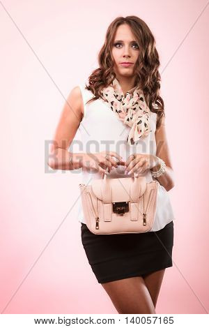 Elegant outfit. Female fashion. Girl in fashionable clothes holding bag handbag studio shot on pink background