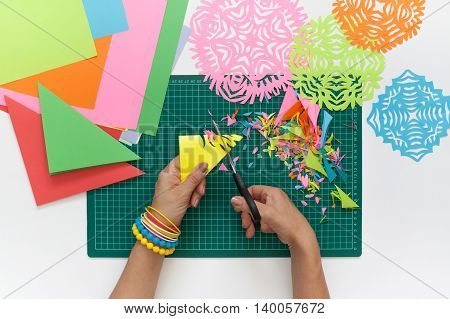 Snowflakes of colored paper. Scissors and cutting mat.