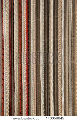 Vertical image in lengths of hanging, colorful braided rope.