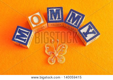 The word mommy spelled with alphabet blocks against an orange background
