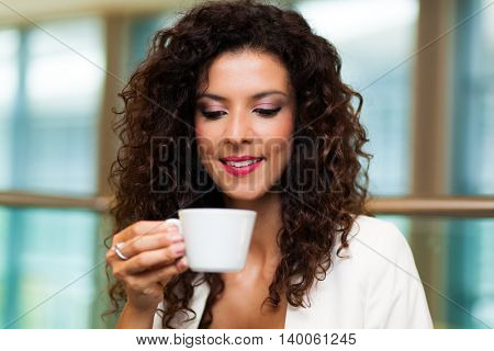 Young woman at home having a cup of coffee