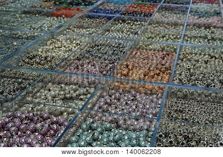 Hundreds of colored beads in clear plastic boxes on display