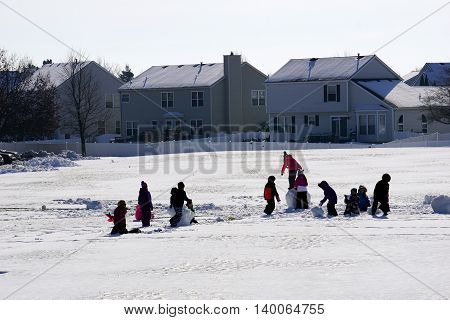 JOLIET, ILLINOIS / UNITED STATES - NOVEMBER 24, 2015: Children play in the snow after a November snowstorm in Joliet.