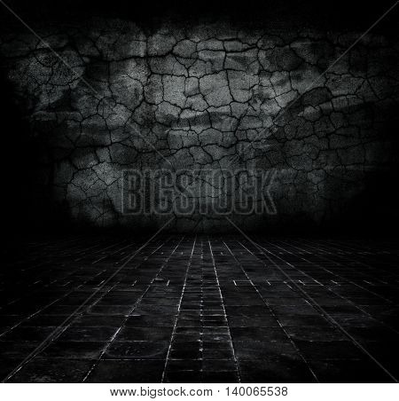 Dark grungy stone room with many cracks forming.