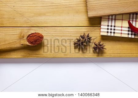 Badian ground paprika and chili peppers on a wooden background
