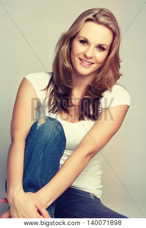 Smiling blond woman wearing jeans and tshirt