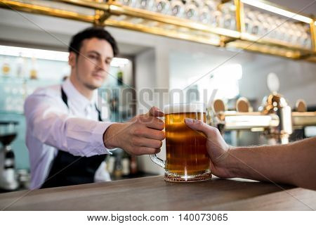 Barkeeper serving beer to male customer at restaurant