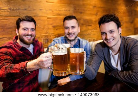 Portrait of young male friends toasting beer at restaurant