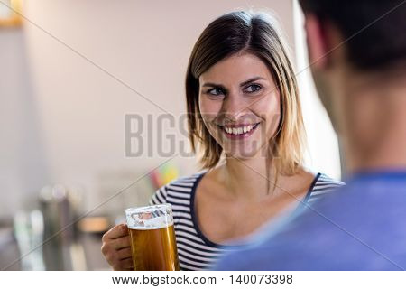 Happy woman looking at boyfriend while drinking beer in bar