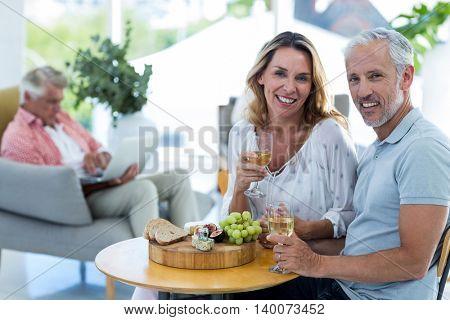 Portrait of happy mature couple having wine in restaurant