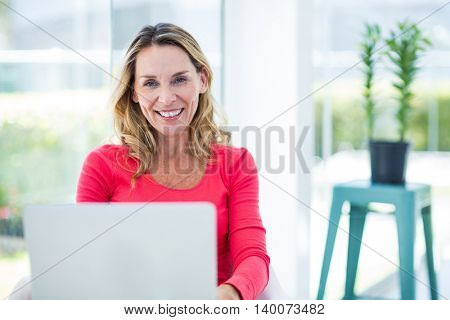 Portrait of woman smiling while using laptop at home