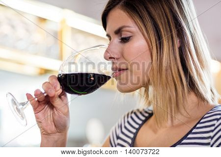 Beautiful young woman drinking wine at restaurant