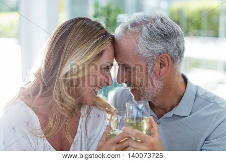 Close-up of romantic mature couple holding wineglass in restaurant