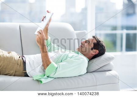 Side view of man using digital tablet while relaxing on sofa at home