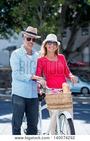Portrait of smiling mature couple with bicycle in city