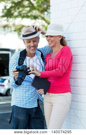 Mature couple looking in camera while standing by wall in city