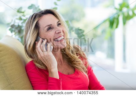 Close-up of smiling woman talking on cellphone at home